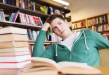 Парень сидит за учебниками