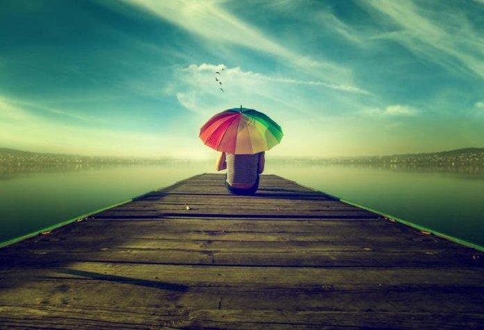 Парень с зонтиком на пирсе