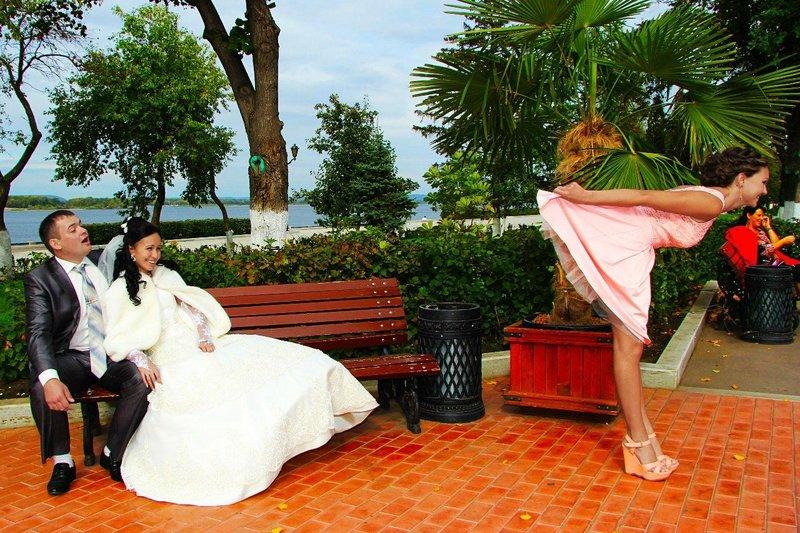 Подружка невесты поднимает платье