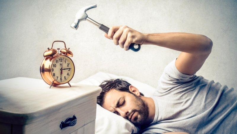 Мужчина ломает будильник молотком