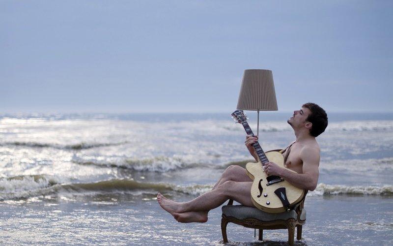 С гитарой на фоне моря