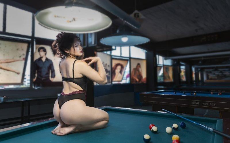 Девушка сидит на бильярдном столе