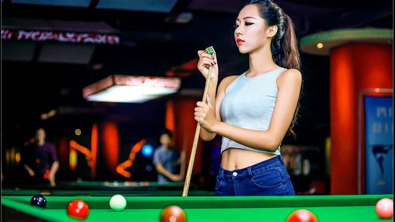 Девушка стоит возле стола для бильярда