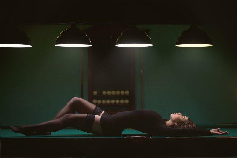 Девушка в черном на бильярном столе