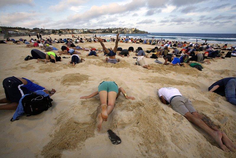 Люди на пляже зарылись с головой