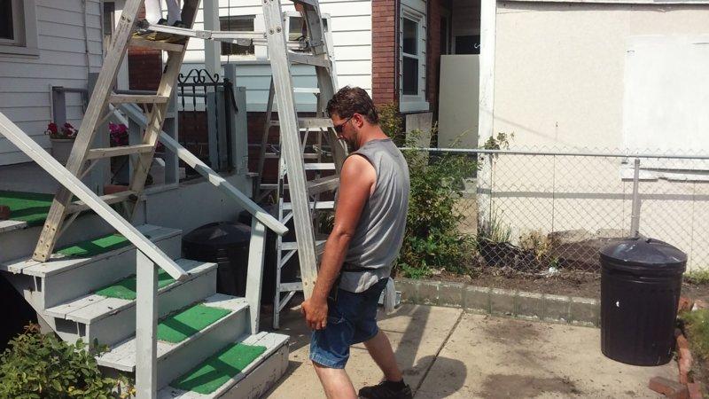 Мужчина держит лестницу