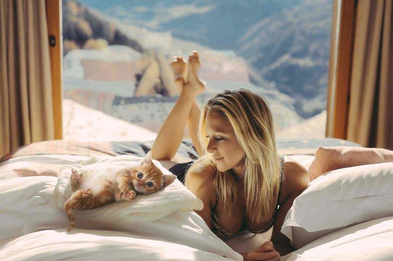 Блондинка с котом на кровати