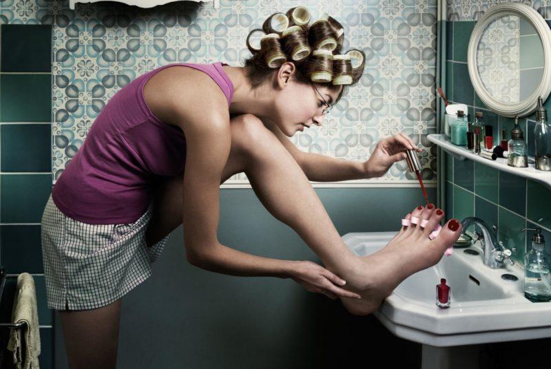 Девушка красит ногти на ногах