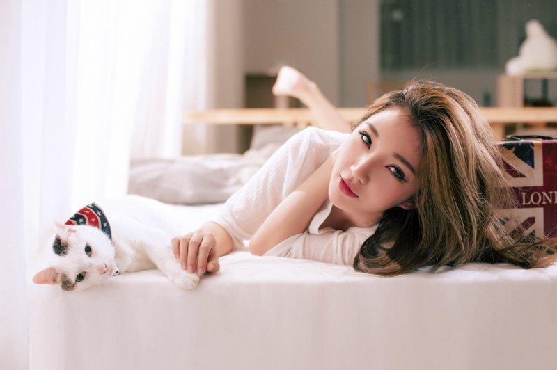 Азиатка с котом на кровати